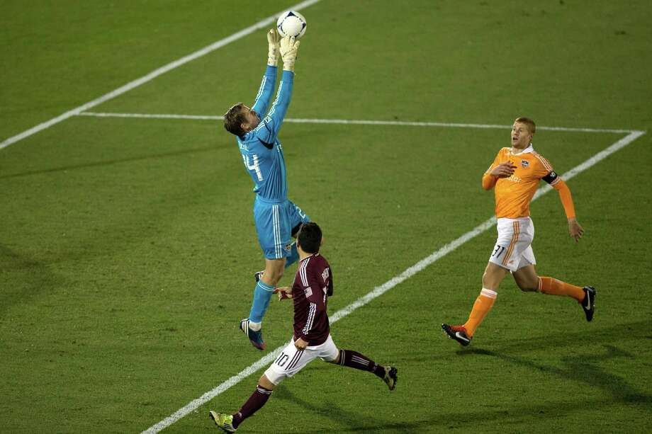 COMMERCE CITY, CO - OCTOBER 27:  Goalkeeper Tyler Deric #24 of the Houston Dynamo grabs the ball out of the air away from Martin Rivero #10 of the Colorado Rapids as Andre Hainault #31 of the Houston Dynamo gives chase during the first half at Dick's Sporting Goods Park on October 27, 2012 in Commerce City, Colorado. Photo: Justin Edmonds, Getty Images / Getty Images North America