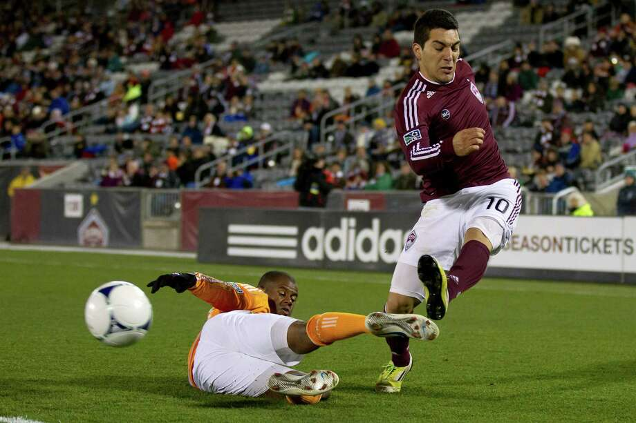 COMMERCE CITY, CO - OCTOBER 27:  Martin Rivero #10 of the Colorado Rapids crosses the ball into the box past a sliding effort by Luiz Camargo #17 of the Houston Dynamo during the first half at Dick's Sporting Goods Park on October 27, 2012 in Commerce City, Colorado. Photo: Justin Edmonds, Getty Images / Getty Images North America