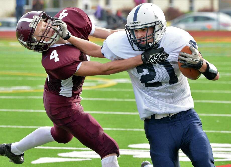 Rensselaer's #21 Tyler Harwood breaks a tackle by Whitehall's #4 Dillon Griffen, left, during Saturday's semifinal game at Schuylerville High School  Oct. 27, 2012.  (John Carl D'Annibale / Times Union) Photo: John Carl D'Annibale / 00019853A