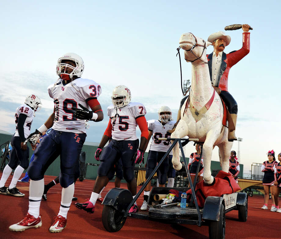 Roosevelt players walk past a statue of Theodore Roosevelt as they enter the field for a district 26-5A football game between the Roosevelt Rough Riders and the Churchill Chargers at Comalander Stadium in San Antonio, Saturday, October 27, 2012.