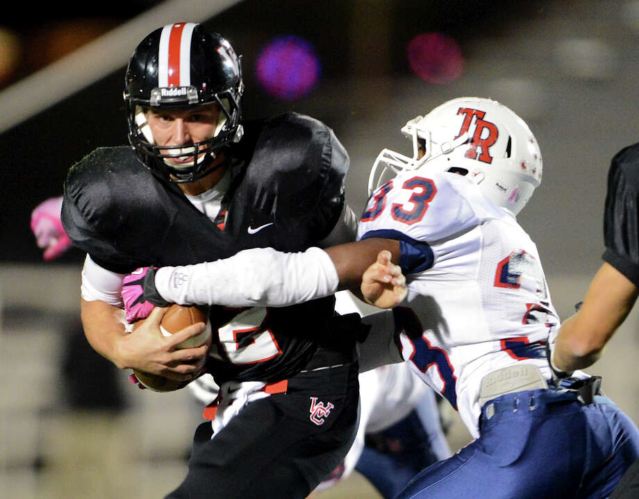 Churchill quarterback Nate Pearson (12) tries to break free of the tackle by Roosevelt's Roy Hodge (33) during a district 26-5A football game between the Roosevelt Rough Riders and the Churchill Chargers at Comalander Stadium in San Antonio, Saturday, October 27, 2012.