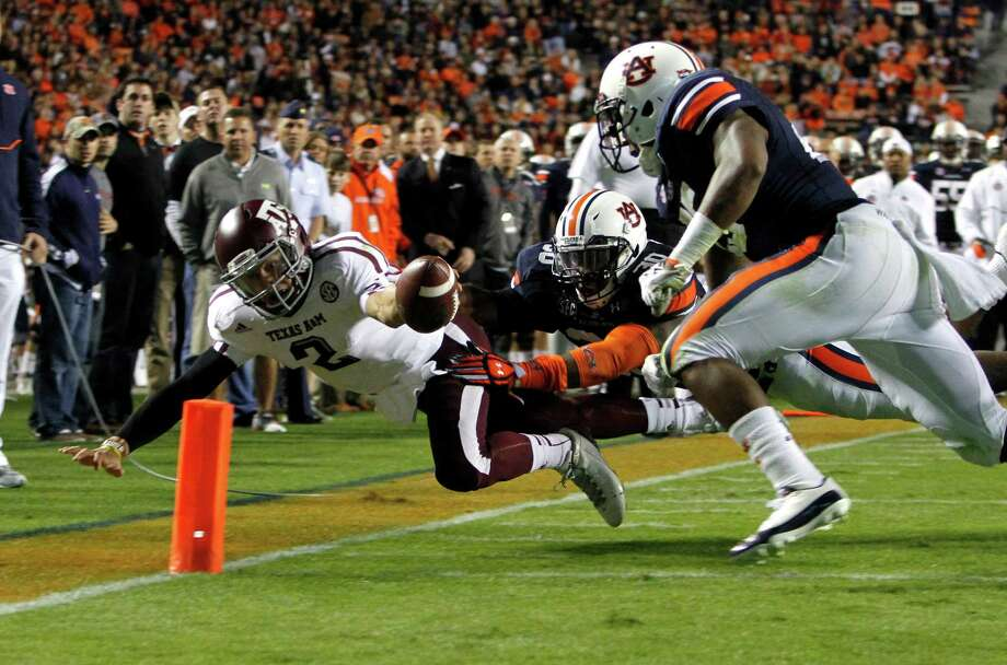 Texas A&M quarterback Johnny Manziel (2) dives for the end zone for a touchdown past Auburn linebacker Cassanova McKinzy (30) and Auburn linebacker Daren Bates (25) during the first half of an NCAA college football game on Saturday, Oct. 27, 2012, in Auburn, Ala. (AP Photo/Butch Dill) Photo: Butch Dill, FRE / FR111446 AP