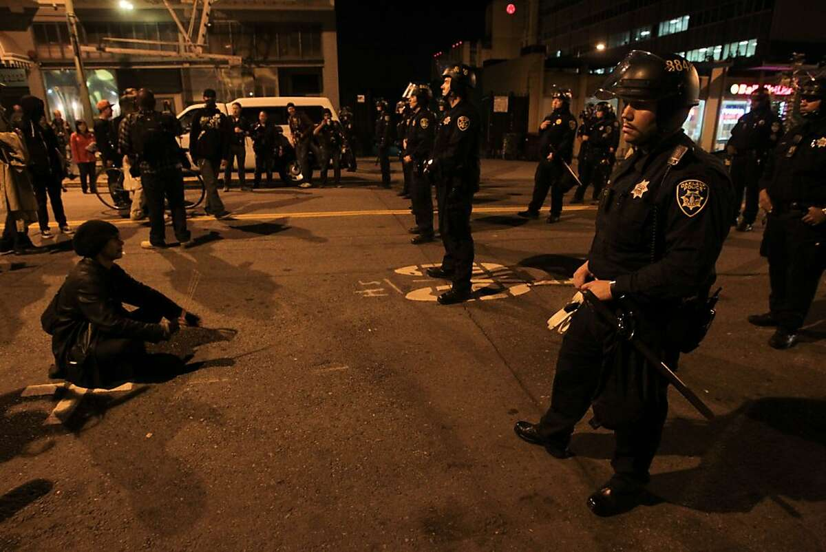 A protester drums on the street in front of a line of police during a march on the one-year anniversary of violent clashes between the Occupy movement and police in Oakland, Calif. on Thursday, Oct. 25, 2012.