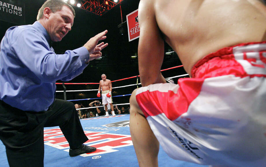 Rocky Juarez (center) looks on as referee Jon D. Schorle II (left) gives Antonio Escalante the count after being hit during the eighth round of their junior lightweight fight held Saturday Oct. 27, 2012 at the Freeman Coliseum. Juarez won with a eighth round TKO. Photo: Edward A. Ornelas, Express-News / © 2012 San Antonio Express-News