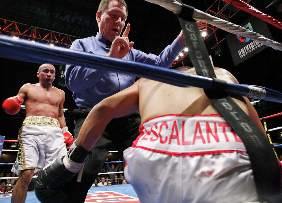 Rocky Juarez (left) looks on as referee Jon D. Schorle II gives Antonio Escalante the count after being hit during the eighth round of their junior lightweight fight held Saturday Oct. 27, 2012 at the Freeman Coliseum. Juarez won with a eighth round TKO. Photo: Edward A. Ornelas, Express-News / © 2012 San Antonio Express-News