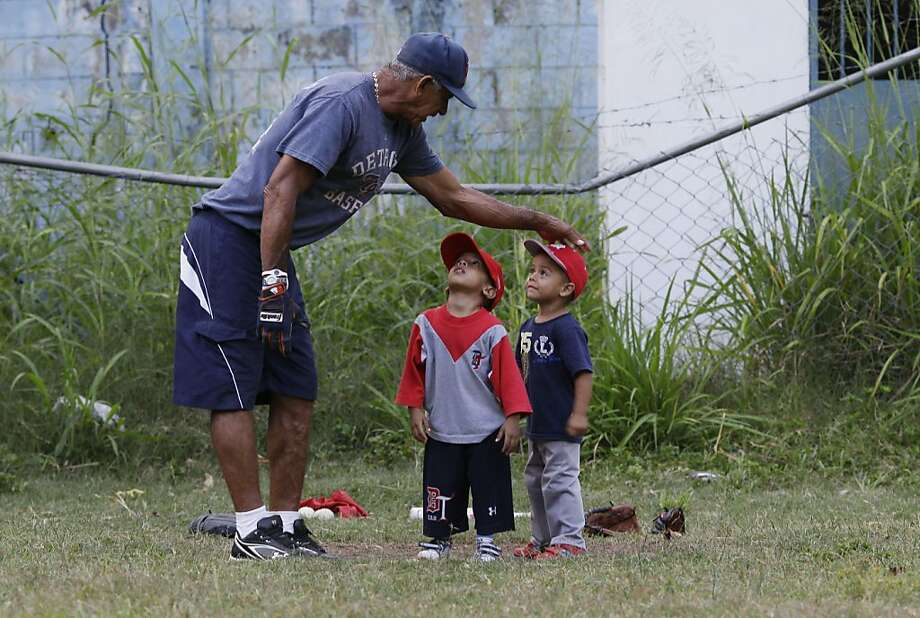 In this Oct. 25, 2012 photo, baseball coach Jose Torres instructs two young boys at a baseball school in Maracay, Venezuela.  Many of the boys are inspired by the example of Detroit Tigers slugger Miguel Cabrera, who learned the game on this very field. Their baseball school in the poor neighborhood where Cabrera grew up is one of many across Venezuela, a web for training young ballplayers that has made the country a powerhouse in the U.S. major leagues. Photo: Ariana Cubillos, Associated Press