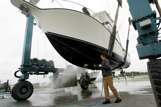 A marina worker rinses off a fishing boat pulled out from the Indian River at the Indian River Marina in Delaware, Md. on Saturday, Oct. 27, 2012 as Hurricane Sandy approaches the Atlantic coast. Photo: Jose Luis Magana