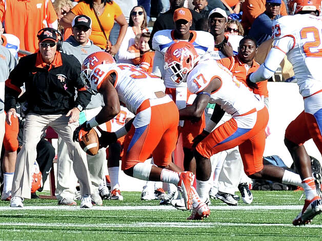SHSU player Robert Shaw causes Lamar running back DePauldrick Garrett to fumble while Kenneth Jenkins, 32, snags the loose ball during the football game between Lamar University and Sam Houston State University at Provost Umphrey Stadium on Saturday, October 27, 2012. Photo taken: Randy Edwards/The Enterprise Photo: Randy Edwards