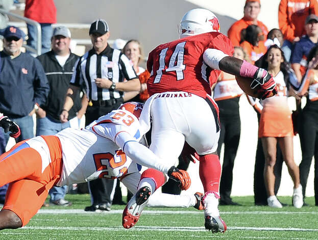 SHSU player Robert Shaw causes Lamar running back DePauldrick Garrett to fumble on a very large gain for the Cardinals during the football game between Lamar University and Sam Houston State University at Provost Umphrey Stadium on Saturday, October 27, 2012. Photo taken: Randy Edwards/The Enterprise Photo: Randy Edwards