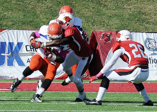 SHSU running back Timothy Flanders is stopped by a group of Lamar defensive players before getting a first down and forcing SHSU to punt during the football game between Lamar University and Sam Houston State University at Provost Umphrey Stadium on Saturday, October 27, 2012. Photo taken: Randy Edwards/The Enterprise