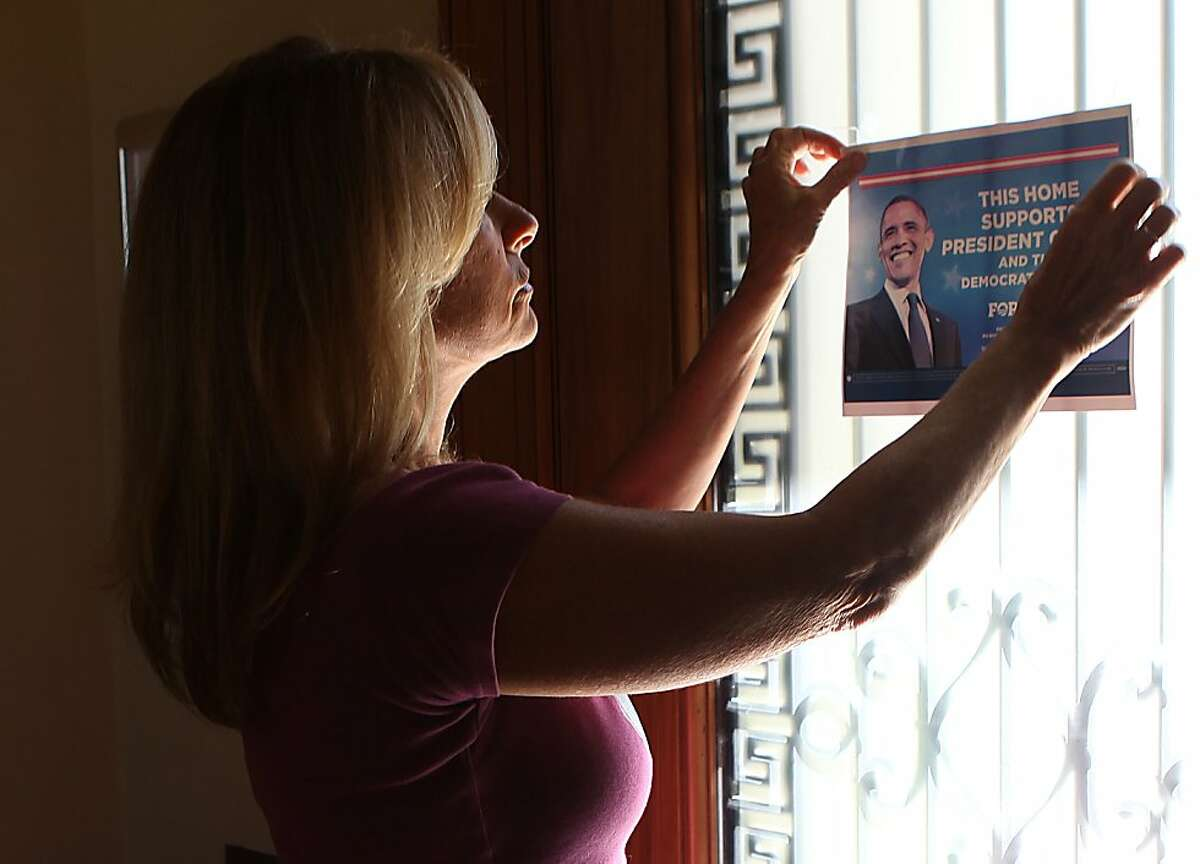 Obama campaign volunteer Kay Edelman switching placement of an Obama poster on her front door in San Francisco, Calif., as she mentions how close the presidential polls are on Thursday, October 25, 2012.
