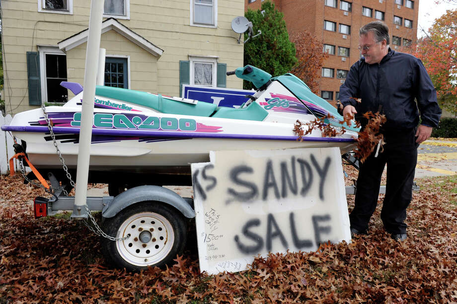 Dean Esposito of Brookfield clears leaves from a waverunner that he has for sale on Main Street in Danbury Sunday, Oct. 28, 2012.  He says with Hurricane Sandy on the way, a waverunner will be a good way to get around if the area floods. Photo: Carol Kaliff