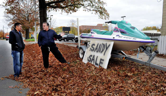 Hector Alvarez of Danbury left, thinks about buying a waverunner for his kids from Dean Esposito of Brookfield on Main Street in Danbury Sunday, Oct. 28, 2012.  With Hurricane Sandy on the way, Esposito is billing his  waverunner as a good way to get around if the area floods. Photo: Carol Kaliff