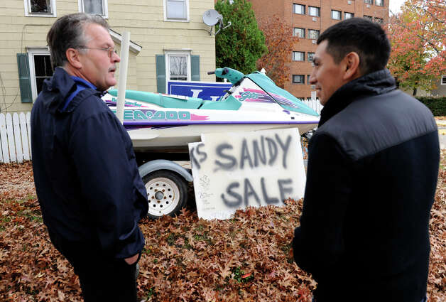 Dean Esposito of Brookfield , left, talks with Hector Alvarez of Danbury right,who is thinking about buying a waverunner for his kids that Esposito has for sale on Main Street in Danbury Sunday, Oct. 28, 2012.  With Hurricane Sandy on the way, Esposito is billing his  waverunner as a good way to get around if the area floods. Photo: Carol Kaliff