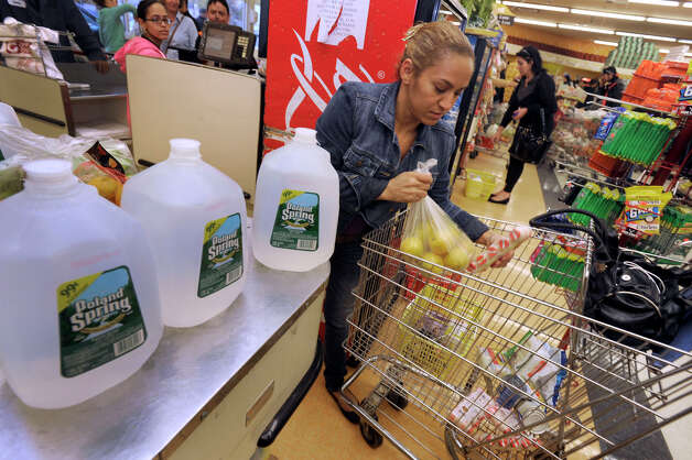 Cleia dos Santos of Danbury, stocks up on water and other esential items at C-Town in Danbury in preparation for Hurricane Sandy, Sunday, Oct. 28, 2012. Photo: Carol Kaliff