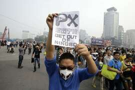 A protester holds up a banner in Zhejiang province's Ningbo city, protesting the proposed expansion of a petrochemical factory Sunday, Oct. 28, 2012. Thousands of people in the eastern Chinese city clashed with police Saturday while protesting the proposed expansion of the factory that they say would spew pollution and damage public health, townspeople said. (AP Photo/Ng Han Guan)