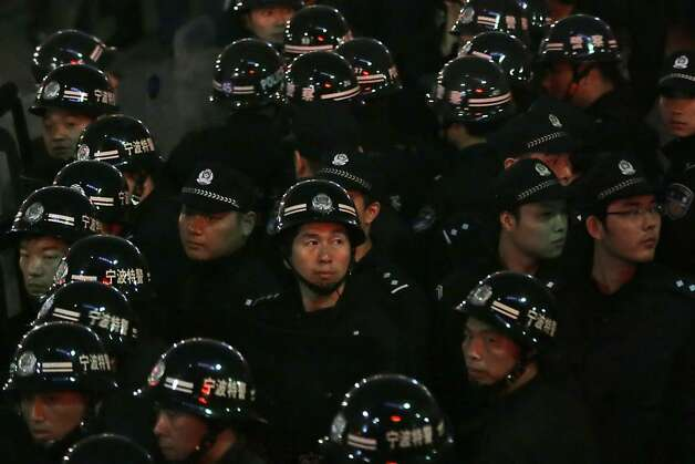 Chinese anti-riot police men gather outside the city government office in Zhejiang province's Ningbo city, where residents had gathered to protest the proposed expansion of a petrochemical factory Sunday, Oct. 28, 2012. Thousands of protesters marched through an eastern Chinese city on Sunday, shouting for fellow citizens to join them in demanding that the government halt the expansion of a petrochemical factory because of pollution fears. (AP Photo/Ng Han Guan) Photo: Ng Han Guan, Associated Press