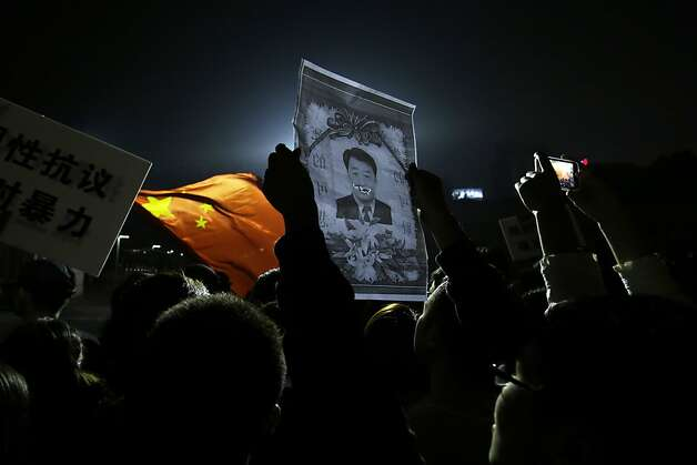 Protesters hold up a defaced picture of the Ningbo city mayor Liu Qi outside the city government office in Zhejiang province's Ningbo city, Sunday, Oct. 28, 2012, where residents had gathered to protest the proposed expansion of a petrochemical factory. Thousands of protesters marched through an eastern Chinese city on Sunday, shouting for fellow citizens to join them in demanding that the government halt the expansion of a petrochemical factory because of pollution fears. (AP Photo/Ng Han Guan) Photo: Ng Han Guan, Associated Press