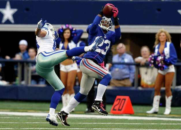 New York Giants cornerback Corey Webster (23) intercepts a pass from Dallas Cowboys quarterback Tony Romo to wide receiver Miles Austin (19) during the first half of an NFL football game Sunday, Oct. 28, 2012 in Arlington, Texas. (AP Photo/Sharon Ellman) Photo: Sharon Ellman, Associated Press / FR170032 AP
