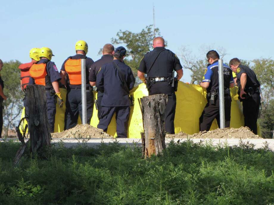 Officials hold up yellow tarps to conceal the body of a woman in her 20s found dead in the San Antonio River Sunday afternoon. Sunday, Oct. 28, 2012. Photo: San Antonio Express-News
