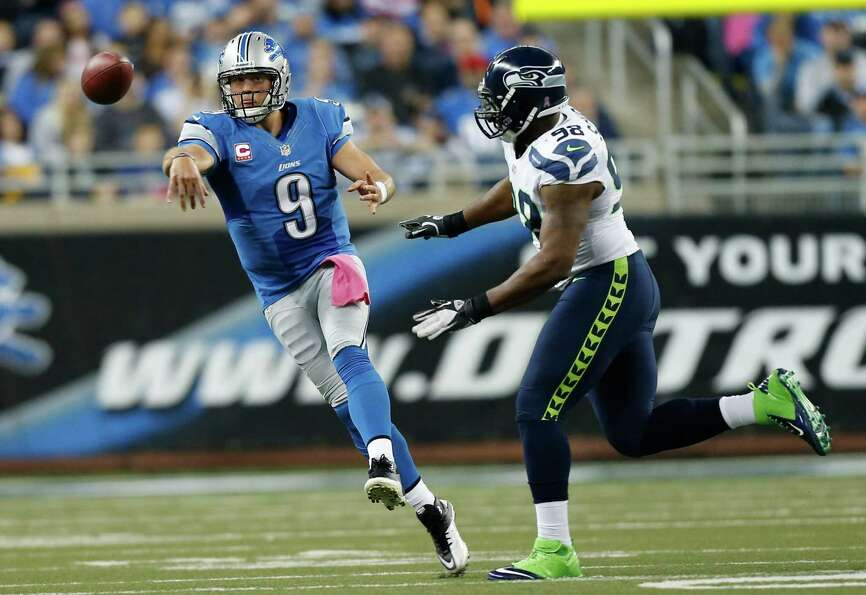Detroit Lions quarterback Matthew Stafford (9) passes as Seattle Seahawks defensive end Greg Scruggs