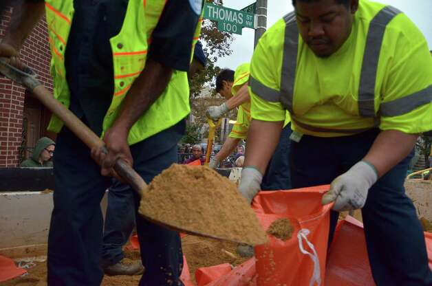"DC Water employees fill bags with sand in downtown Washington, DC October 28, 2012 ahead of Hurricane Sandy's landfall as flooding was expected throughout parts of the US capital.  US emergency officials braced for the potentially massive impact of a so-called ""Frankenstorm"" Sunday as Hurricane Sandy lumbered north in the Atlantic Ocean, poised to hit the Eastern Seaboard with torrential rains and gale-force winds.  The superstorm was expected to make landfall somewhere between Virginia and Massachusetts early in the week, possibly causing chaos during the frenzied last days of campaigning before the November 6 US presidential vote. AFP PHOTO / Eva HAMBACHEVA HAMBACH/AFP/Getty Images Photo: EVA HAMBACH, AFP/Getty Images / AFP"
