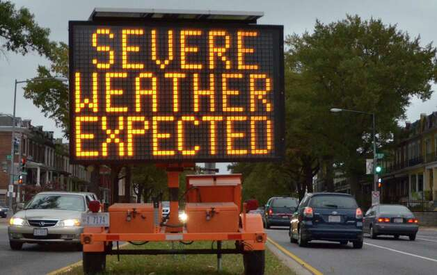 """A road sign warns drivers of weather conditions in downtown Washington, DC October 28, 2012 ahead of Hurricane Sandy's landfall.  US emergency officials braced for the potentially massive impact of a so-called """"Frankenstorm"""" Sunday as Hurricane Sandy lumbered north in the Atlantic Ocean, poised to hit the Eastern Seaboard with torrential rains and gale-force winds.  The superstorm was expected to make landfall somewhere between Virginia and Massachusetts early Tuesday, possibly causing chaos during the frenzied last days of campaigning before the November 6 US presidential vote. AFP PHOTO / Eva HAMBACHEVA HAMBACH/AFP/Getty Images Photo: EVA HAMBACH, AFP/Getty Images / AFP"""