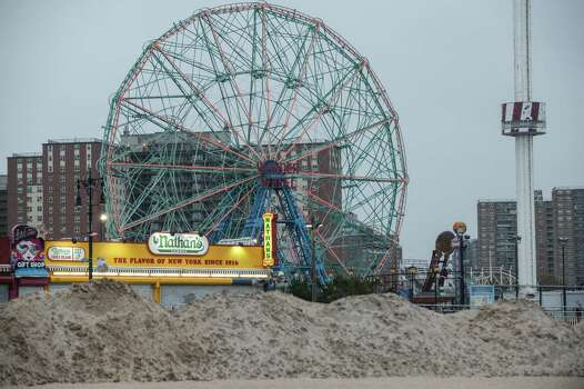 The Coney Island boardwalk is protected by a sand berm ahead of Hurricane Sandy in New York, Oct. 28, 2012. The computer models forecasting the track of Hurricane Sandy over the next three days are converging upon a landing around southern New Jersey that could create record coastal flooding and a big enough storm surge that state and local officials have ordered mandatory and voluntary evacuations along the coast from Delaware to Connecticut. (Robert Stolarik/The New York Times) Photo: ROBERT STOLARIK, NYT / NYTNS