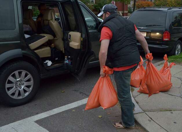 "A resident picks up bags of sand which were being distributed by the local water & sewer authorities in downtown Washington, DC October 28, 2012 ahead of Hurricane Sandy's landfall as flooding was expected throughout parts of the US capital.  US emergency officials braced for the potentially massive impact of a so-called ""Frankenstorm"" Sunday as Hurricane Sandy lumbered north in the Atlantic Ocean, poised to hit the Eastern Seaboard with torrential rains and gale-force winds.  The superstorm was expected to make landfall somewhere between Virginia and Massachusetts early in the week, possibly causing chaos during the frenzied last days of campaigning before the November 6 US presidential vote.  AFP PHOTO / Eva HAMBACHEVA HAMBACH/AFP/Getty Images Photo: EVA HAMBACH, AFP/Getty Images / AFP"