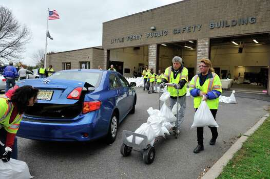 10/28/2012    Little Ferry, NJ    4:5    At the first aid squad in Little Ferry, members hand out three sandbags each to residents in preparation for flooding due to Hurricane Sandy.   Little Ferry 1st Aid Squad members Bobby Steinhilber and Elsie Coons, right, hand out three sandbags each to residents in preparation for flooding due to Hurricane Sandy.     CHRIS MONROE/SPECIAL TO THE RECORD Photo: CHRIS MONROE/SPECIAL TO THE RECO, Consortium / The Record (Bergen Co., N.J.)