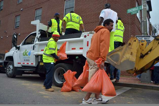 "A resident picks up bags of sand which were being distributed by the local water & sewer authorities in downtown Washington, DC October 28, 2012 ahead of Hurricane Sandy's landfall as flooding was expected throughout parts of the US capital.  US emergency officials braced for the potentially massive impact of a so-called ""Frankenstorm"" Sunday as Hurricane Sandy lumbered north in the Atlantic Ocean, poised to hit the Eastern Seaboard with torrential rains and gale-force winds.  The superstorm was expected to make landfall somewhere between Virginia and Massachusetts early in the week, possibly causing chaos during the frenzied last days of campaigning before the November 6 US presidential vote. AFP PHOTO Eva HAMBACHEVA HAMBACH/AFP/Getty Images Photo: EVA HAMBACH, AFP/Getty Images / AFP"