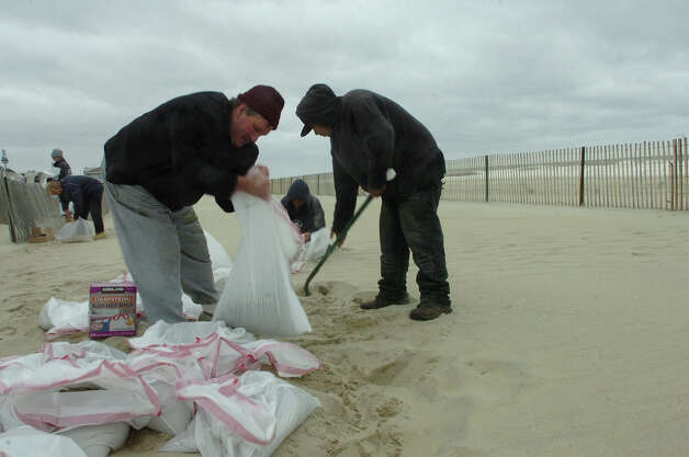 """Belmar, New Jersey, resident Jim Calogero fills sandbags at the beach which he planned to use to fortify his nearby home from the expected floodwaters on Sunday, October 28, 2012. Calogero has lived near the beach for 25 years but says """"we've never had anything like this,"""" referring to Hurricane Sandy. (Kate Collins) Photo: Consortium / The Record (Bergen Co., N.J.)"""