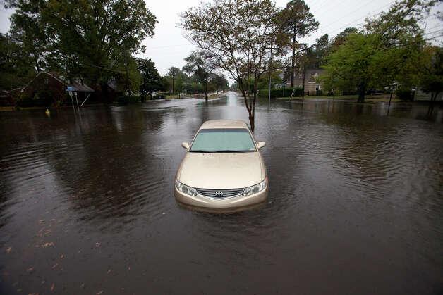 High water from Hurricane Sandy surrounds a car along Hampton Boulevard in Norfolk, Va., near Larchmont Crescent, Sunday morning, Oct. 28, 2012. Photo: Bill Tiernan, AP / The Virginian-Pilot