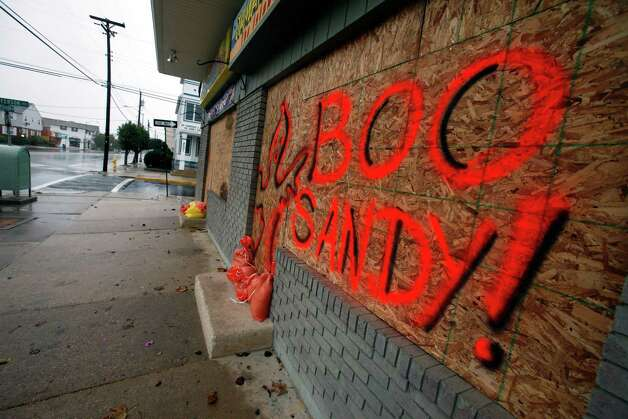 """The boarded up windows on a store front in Margate N.J., read """"Boo Sandy!"""", as the area prepares for the arrival of the superstorm, Sunday, Oct. 28, 2012. Photo: Joseph Kaczmarek, AP / FR109827 AP"""