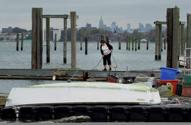 Debbie Anderson tie lines on a dock on City Island October 28, 2012 in New York.  As Hurricane Sandy moves closer the East Coast millions of people across nine states are preparing for the super-storm's torrential rains, high winds, major flooding, power outages and heavy snow about a week before the presidential election. AFP PHOTO/DON EMMERTDON EMMERT/AFP/Getty Images Photo: DON EMMERT, AFP/Getty Images / AFP