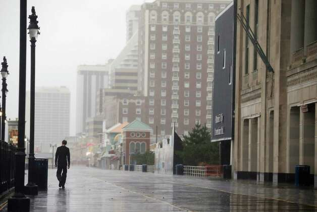 ATLANTIC CITY, NJ - OCTOBER 28: A man walks on the boardwalk ahead of Hurricane Sandy on October 28, 2012 in Atlantic City, New Jersey. Governor Chris Christie?s emergency declaration is shutting down the city?s casinos and 30,000 residents are being told to evacuate. Photo: Mario Tama, Getty Images / 2012 Getty Images
