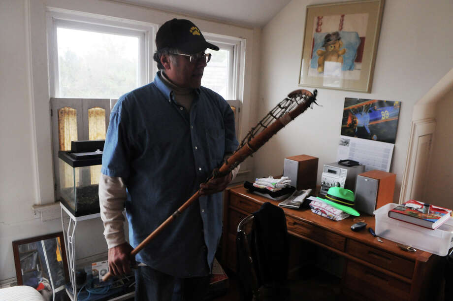 Frank Acello looks over a lacrosse stick used by his late wife during her college years. Acello made items reminiscent of her a priority in his preparation for possible flooding as Hurricane Sandy approaches Stamford, Conn., October 28, 2012.  Mayor Michael Pavia declared a state of emergency and ordered residents of the much of the shoreline, including Eureka Terrace where Acello lives, to evacuate their homes and seek higher ground. Photo: Keelin Daly