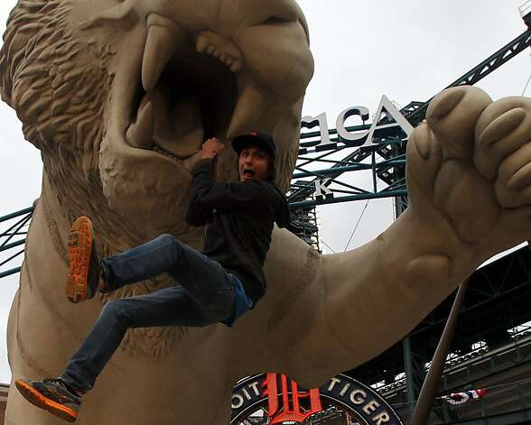 Yves L'Heureux hands from the tooth of a giant Tiger outside the main gates of Comerica Park in Detroit, Mi, hours before the start of game four of the World Series between the San Francisco Giants and Detroit Tigers Sunday, Oct. 28, 2012. Photo: Lance Iversen, The Chronicle
