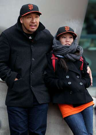 San Francisco Giants fans Jonathan Lee and Suzy Choi try to stay warm while waiting for the gates to open at Comerica Park in Detroit, Mi, and Sunday, Oct. 28, 2012. Photo: Lance Iversen, The Chronicle