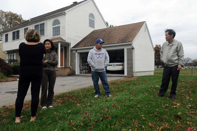 Tupper Drive neighbors, from left, Maria Raus, Grace Ong, Dennis McMahon and Joe Ong, discuss how to protect their homes from Hurricane Sandy in Stamford, Conn., October 28, 2012.  Mayor Michael Pavia declared a state of emergency and ordered residents of the much of the shoreline to evacuate their homes and seek higher ground. Photo: Keelin Daly