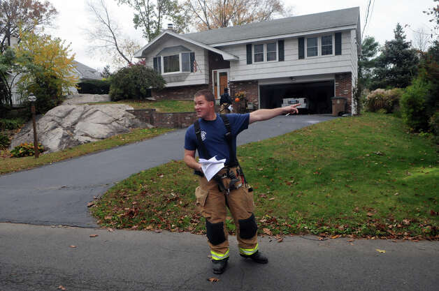 Stamford Fire and Rescue Captain Jacques Roy works to alert homeowners on Tupper Drive of a mandatory evacuation as the city prepares for Hurricane Sandy in Stamford, Conn., October 28, 2012.  Mayor Michael Pavia declared a state of emergency and ordered residents of the much of the shoreline to evacuate their homes and seek higher ground. Photo: Keelin Daly