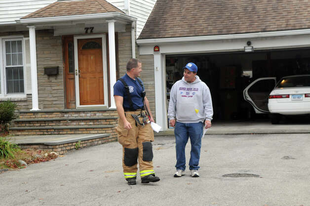 Stamford Fire and Rescue Captain Jacques Roy speaks with Dennis McMahon as he alerts homeowners on Tupper Drive of a mandatory evacuation as the city prepares for Hurricane Sandy in Stamford, Conn., October 28, 2012.  Mayor Michael Pavia declared a state of emergency and ordered residents of the much of the shoreline to evacuate their homes and seek higher ground. Photo: Keelin Daly