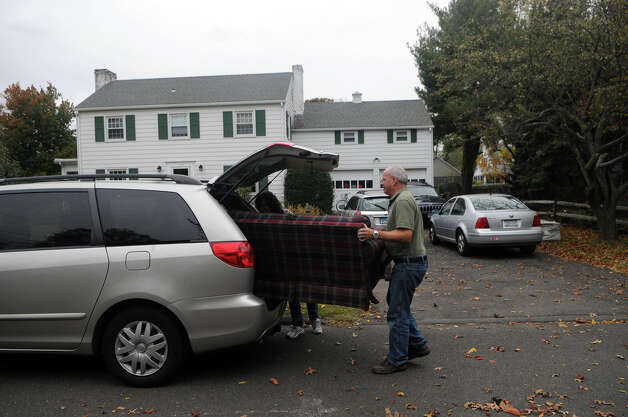 Bill Malloy and his daughter Suzanne Valeski load a couch into a car as they prepare for Hurricane Sandy in Stamford, Conn., October 28, 2012. Malloy lives on Ralsey Road which was on the city's evacuation list. Mayor Michael Pavia declared a state of emergency and ordered residents of the much of the shoreline to evacuate their homes and seek higher ground. Photo: Keelin Daly