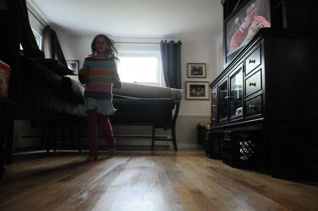 Karina Valeski, 9, runs past the furniture in her grandparent's home which was raised onto chairs and crates in preparation for Hurricane Sandy in Stamford, Conn., October 28, 2012. Mayor Michael Pavia declared a state of emergency and ordered residents of the much of the shoreline to evacuate their homes and seek higher ground. Photo: Keelin Daly