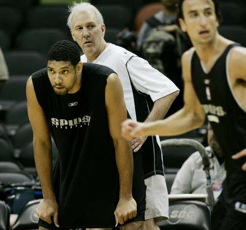 Spurs coach Gregg Popovich, center, watches over forward Tim Duncan, left, and guard Manu Ginobili, of Argentina, during practice in San Antonio, Saturday, June 11, 2005. The Spurs will face the Detroit Piston in game 2 of the NBA Finals Sunday. (AP Photo/Eric Gay) (AP)
