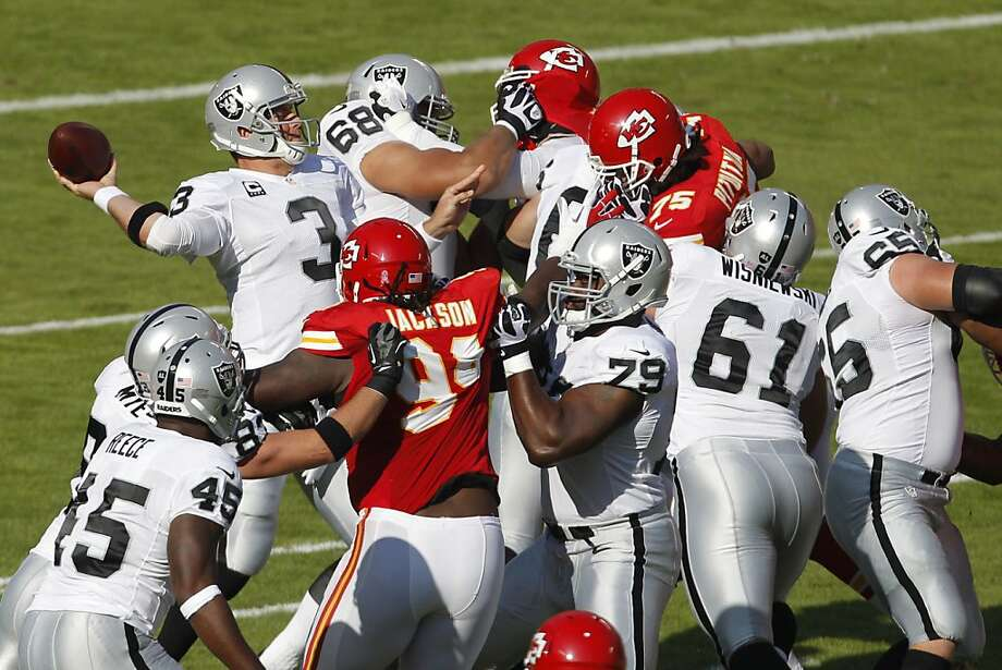 Carson Palmer unleashes a first-half pass behind a wall of teammates. He was not sacked. Photo: Ap, Associated Press
