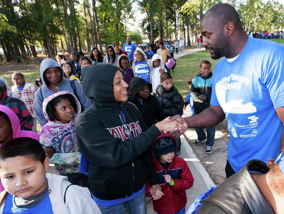 Councilman Jerry Davis welcomes participants to the inaugural Walking Toward Literacy event at Tidwell Park on Saturday.  The event was held to draw attention to the needs of his district. Photo: J. Patric Schneider, Freelance / Houston Chronicle