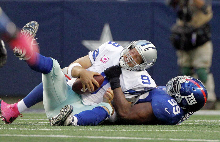 New York Giants defensive tackle Chris Canty (99) sacks Dallas Cowboys quarterback Tony Romo (9) during the second half of an NFL football game Sunday, Oct. 28, 2012 in Arlington, Texas. (AP Photo/Tony Gutierrez) Photo: Tony Gutierrez, Associated Press / AP