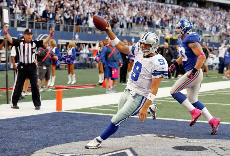 Dallas Cowboys quarterback Tony Romo (9) gets past New York Giants middle linebacker Chase Blackburn (93) to score a touchdown during the second half of an NFL football game Sunday, Oct. 28, 2012 in Arlington, Texas. (AP Photo/Sharon Ellman) Photo: Sharon Ellman, Associated Press / FR170032 AP