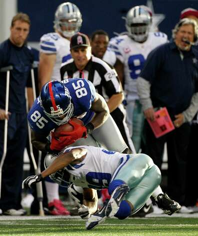 Dallas Cowboys cornerback Brandon Carr (39) tackles New York Giants tight end Martellus Bennett (85) after a reception in the second half of a NFL football game Sunday, Oct. 28, 2012, in Arlington, Texas. The Giants defeated the Cowboys 29-24. (AP Photo/Tony Gutierrez) Photo: Tony Gutierrez, Associated Press / AP